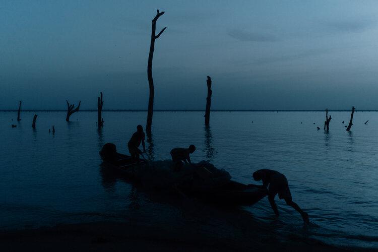 Boys of Volta pushing a boat