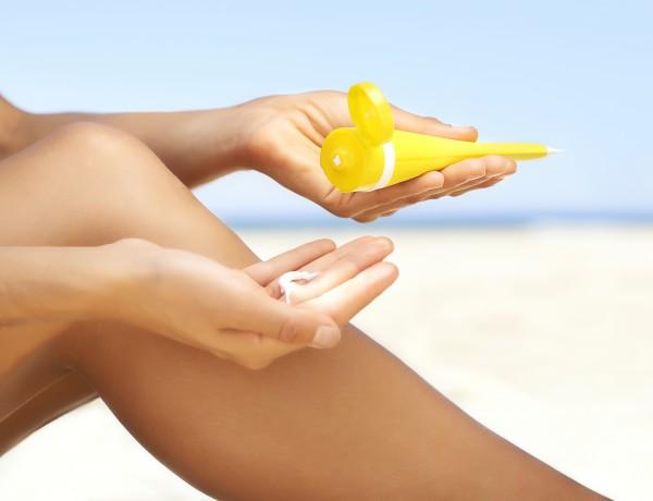 Woman applying sun cream to legs