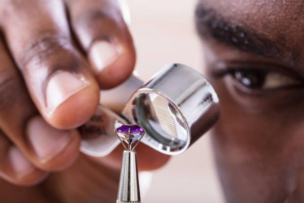 African-American jeweler examining diamond through loupe